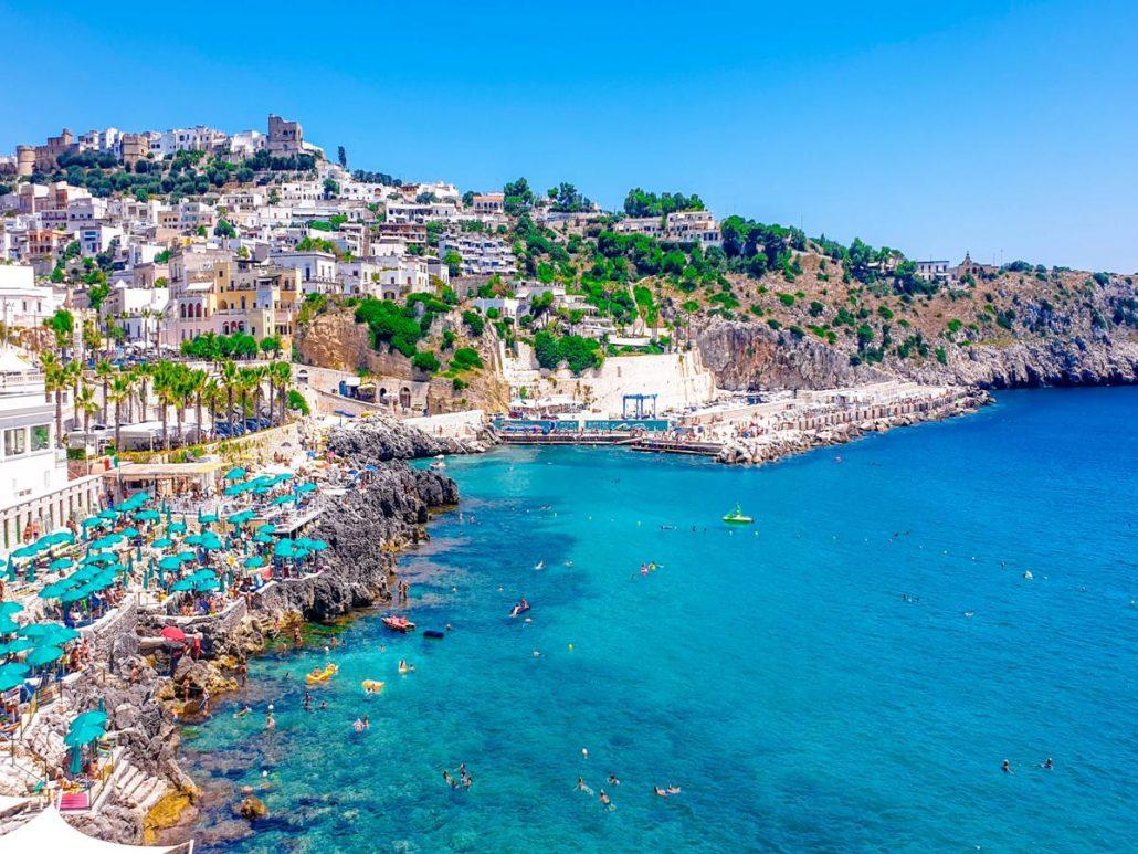 castro marina, scogliera con ombrelloni e alberi, borgo sul mare, mare blu cobalto