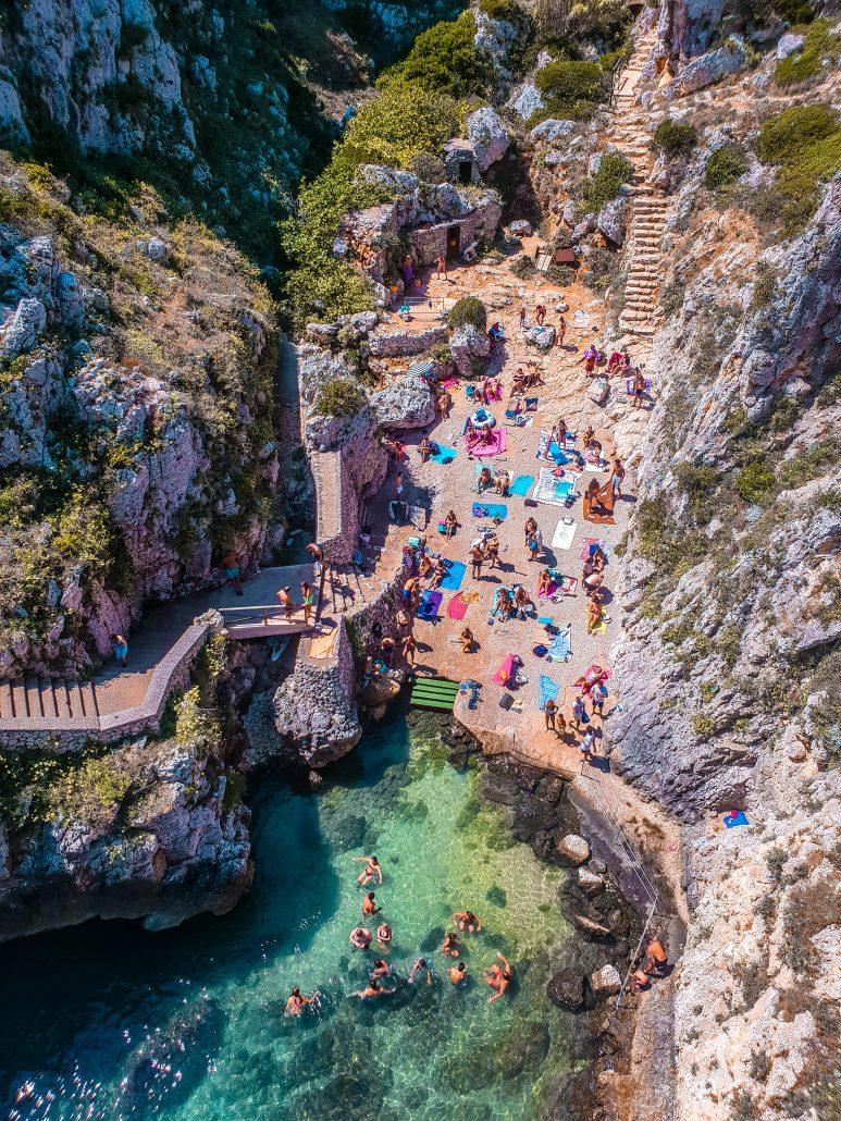 Ponte ciolo visto dall'alto, piccola baia con persone, acqua smeraldo e roccia circostante