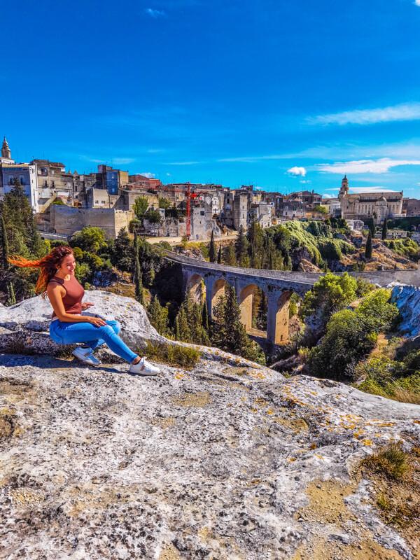 persona seduta sulla gravina con vista ponta dell'acquedotto