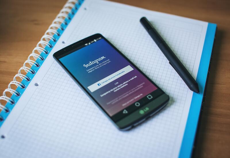 cellulare con instagram su un'agenda e una penna