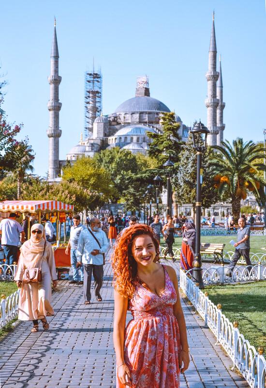 ragazza in primo piano con moschea blu sullo sfondo