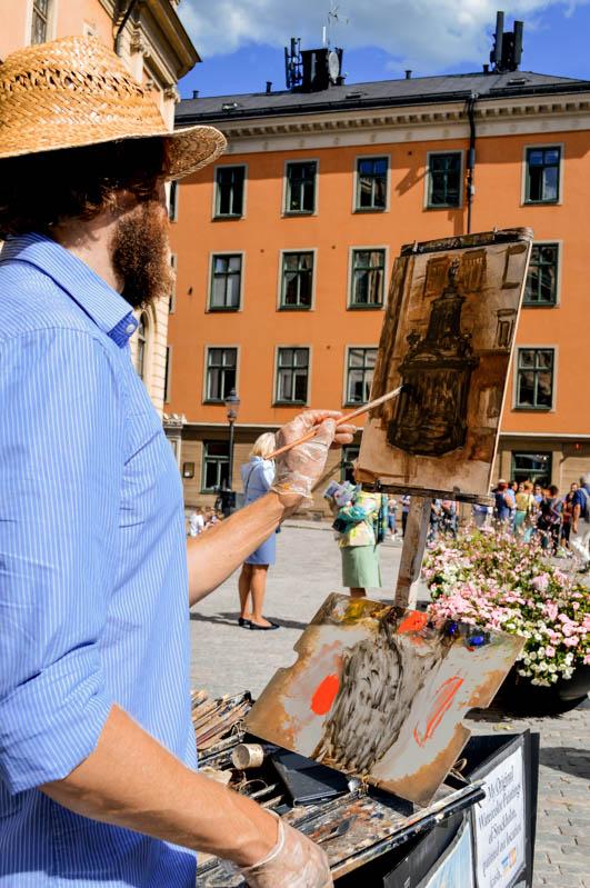 artista che dipinge nella piazza a gamla stan